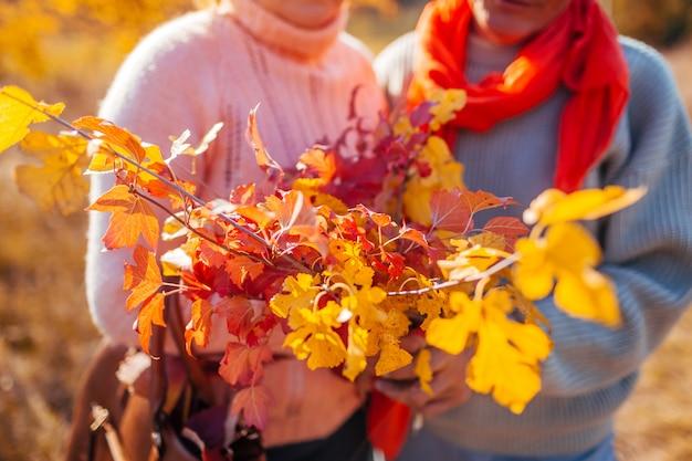 黄色と赤の葉と秋の枝の花束を保持している中年夫婦