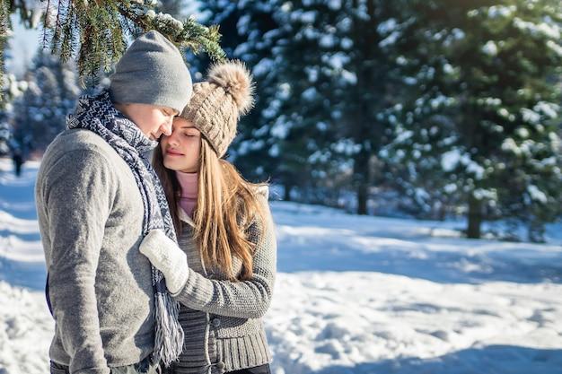 愛のカップルは冬の森で抱擁します。