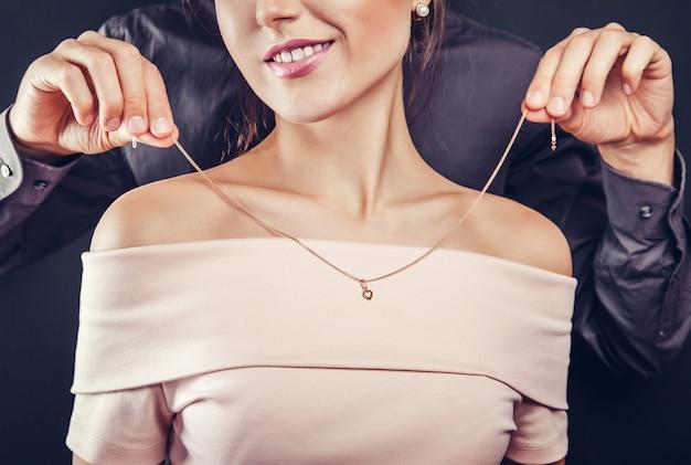 金色のネックレスを試着するために彼のガールフレンドを助ける男。バレンタインデーのギフト。