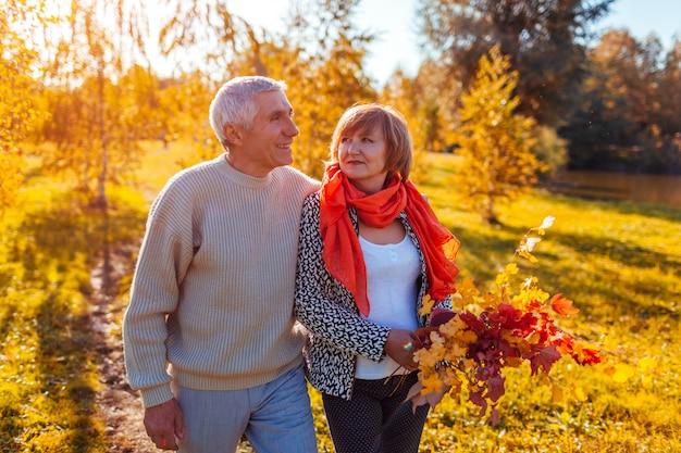 秋の森を歩くハッピーシニアカップル