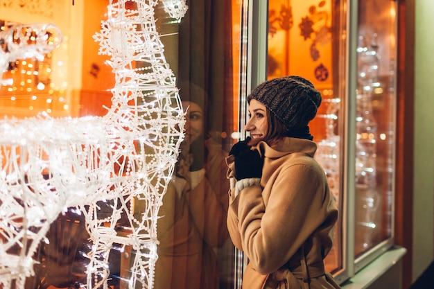 街を歩いて、夜に飾られたクリスマスショーケースを見て若い女性。