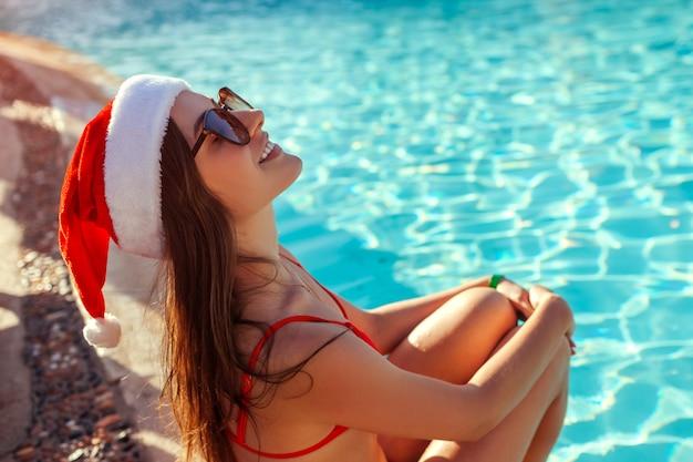 新年とクリスマス休暇。スイミングプールでリラックスしたサンタさんの帽子とビキニの女性。熱帯のお祭り休暇