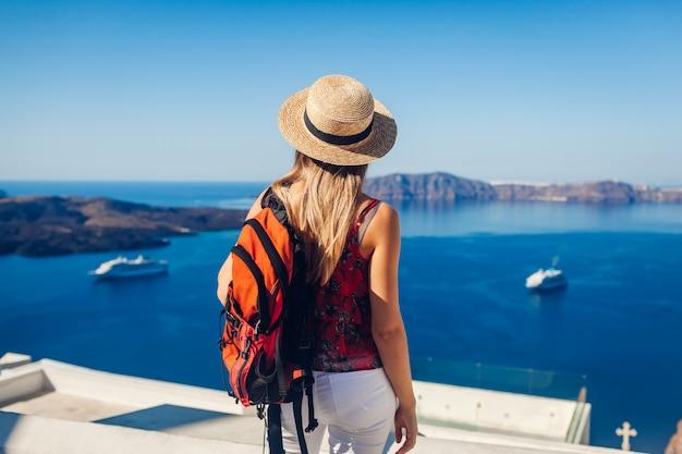 フィラまたはテラ、サントリーニ島、ギリシャからカルデラを見ている女性旅行者。観光、旅行、休暇の概念
