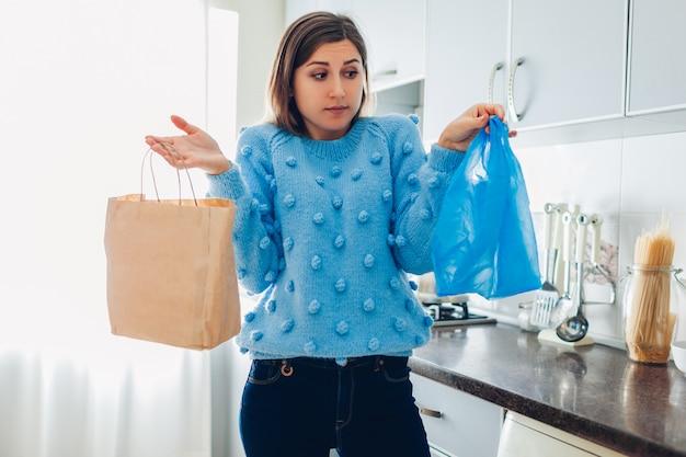 Выбор пластикового или бумажного пакета. женщина, выбирая между эко и полиэтиленовый пакет на кухне