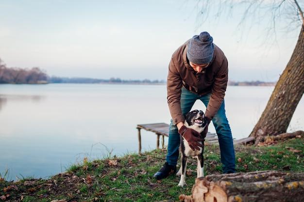 湖で秋の公園で犬と遊ぶ男。楽しんで幸せなペット屋外で歩く