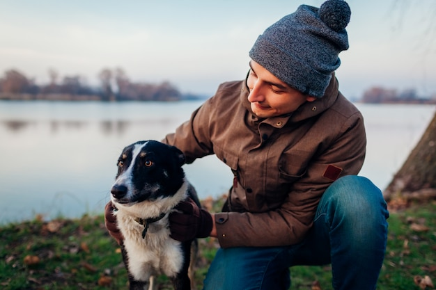 湖で秋の公園で犬と遊ぶ男。屋外楽しんで幸せなペット