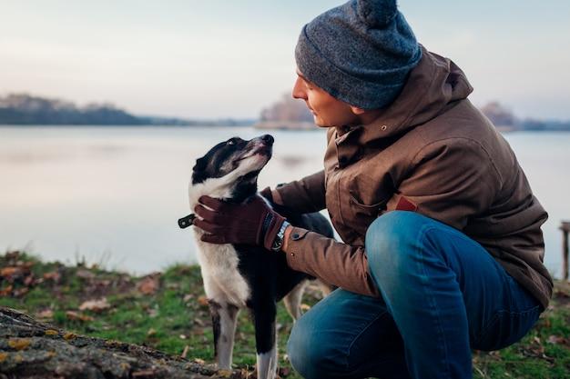 湖のそばの秋の公園で犬を歩く男。屋外楽しんで幸せなペット