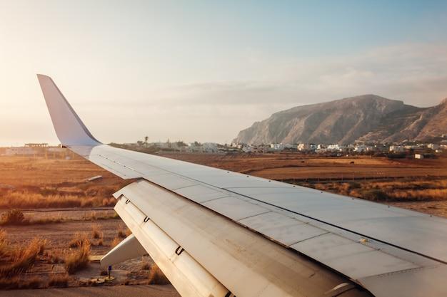 サントリーニ島のフィラに着陸する飛行機。飛行機の翼の眺め。旅行のコンセプト