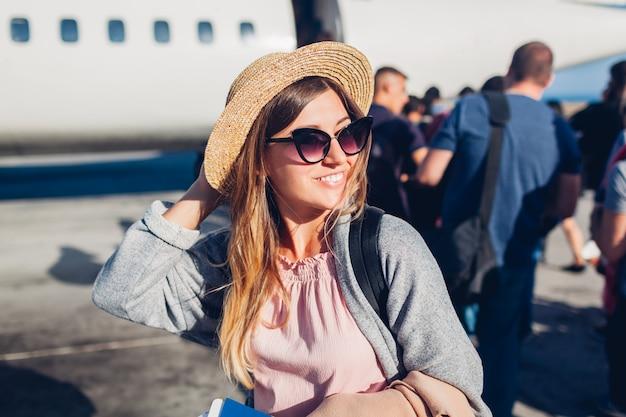 パスポートを保持している飛行機に搭乗する女性旅行者。フライトの準備ができて並んでバックパックで幸せな乗客