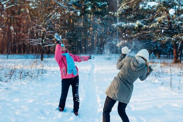 Снежки играют в зимнем лесу. семья мать и дочь весело бросать снег на открытом воздухе
