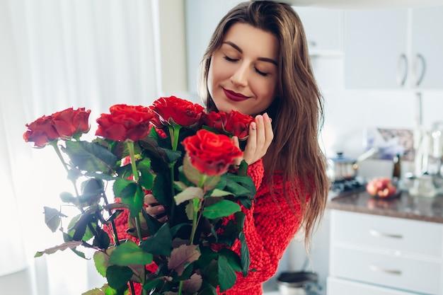 День святого валентина. молодая женщина нашла букет красных роз на кухне. счастливая девушка держит и пахнущие цветы.