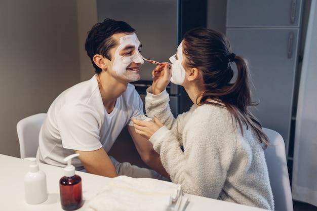 Женщина, применяя глиняную маску на лице мужа. молодая любящая пара, заботящаяся о коже дома. здоровая рутина