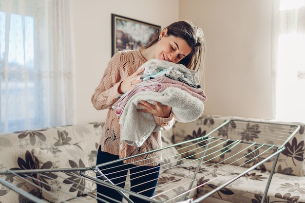 Счастливая женщина, пахнущие собрал чистую одежду из сушилки в кучу