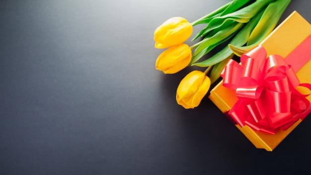 Подарочная коробка с красным бантом и букетом тюльпанов