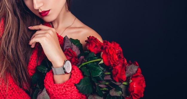 赤いバラの花束を保持している女性