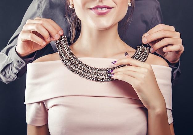 宝石のネックレスを試着する彼のガールフレンドを助ける男