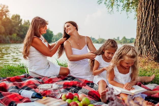 Мама, бабушка и дети плетут косички друг другу