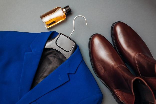 革の靴、青いジャケット、香水