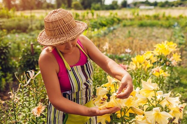 庭の花の世話をする年配の女性