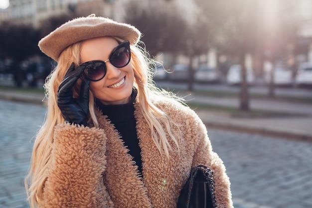 Стильная женщина в плюшевом пальто берет солнцезащитные очки и держит сумочку на открытом воздухе