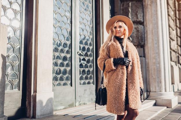 Стильная женщина, идущая в шляпе тедди и держащая сумочку на открытом воздухе
