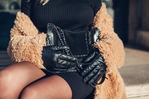 スタイリッシュな女性のコートを着て、黒の財布を屋外に保持