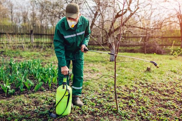 春の庭で昆虫に対して木を散布するために手動農薬散布機をポンプで運ぶ農夫。農業および園芸