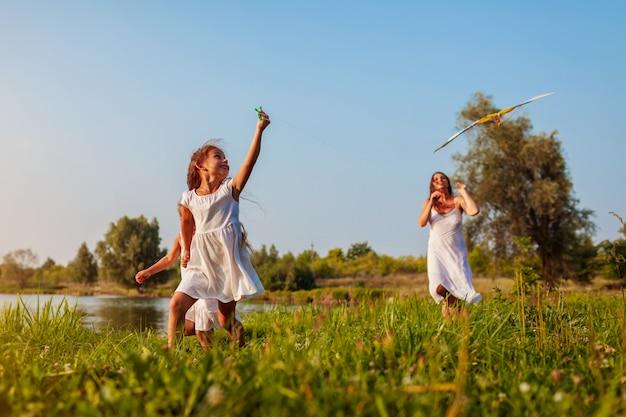 День матери. счастливые девушки бегают с кайтом в парке летом, пока мама помогает им. дети веселятся на свежем воздухе
