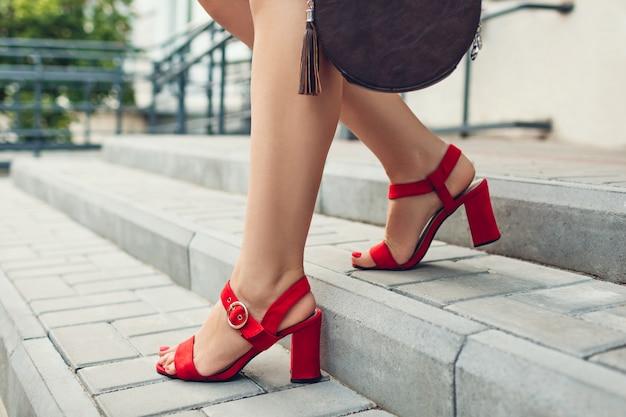 Стильная обувь и аксессуары. молодая женщина носить модные красные босоножки на высоком каблуке и держа сумочку