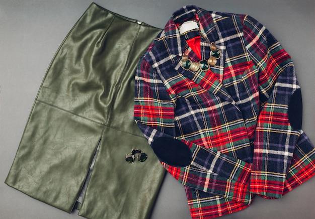 女性のためのファッション衣装。トレンディなレザーグリーンスカート、ストライプジャケット、ジュエリー。春の女性服アクセサリー。