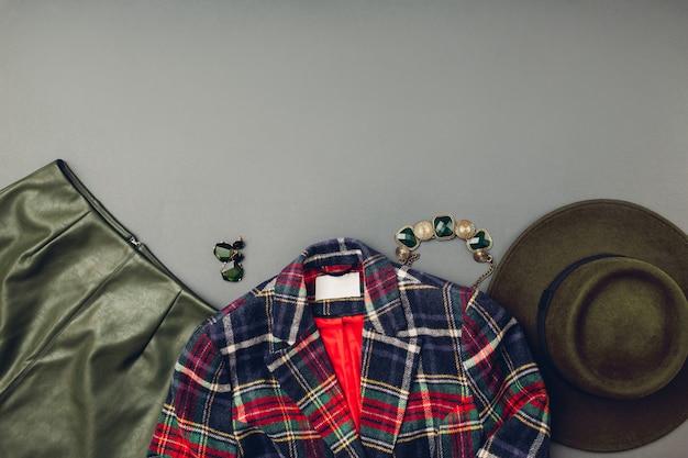 女性のためのファッション衣装。流行の革の緑のスカート、帽子、縞模様のジャケット、ジュエリー。春の女性服アクセサリー。