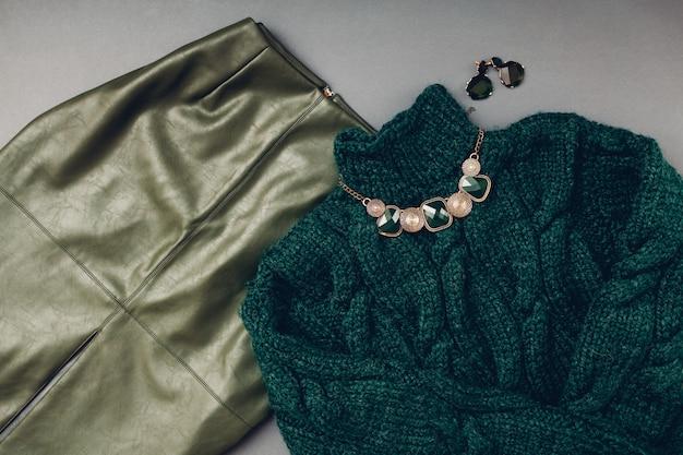 女性のためのファッション衣装。トレンディな革グリーンスカート、セーター、ジュエリー。春の女性服アクセサリー。
