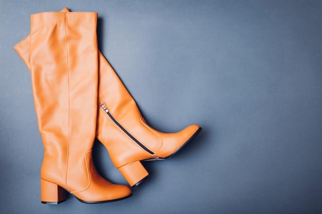 女性のための靴、スタイリッシュな革のブーツ。女性の冬、秋、春のファッション。オレンジのキャラメル靴。スペース