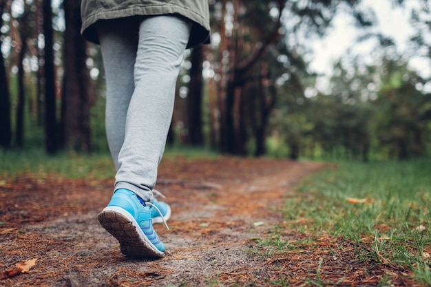 春の森を歩く女性観光客靴のクローズアップ旅行と観光