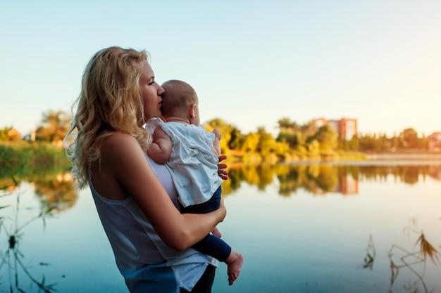 День матери. молодая женщина держа и обнимая ребёнок рекой весны.