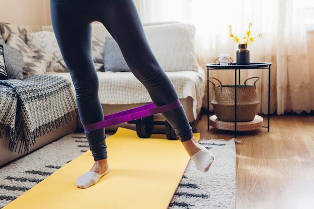 コロナウイルス検疫中の自宅トレーニング。マットスポーツベルトを使用して女性のトレーニング。