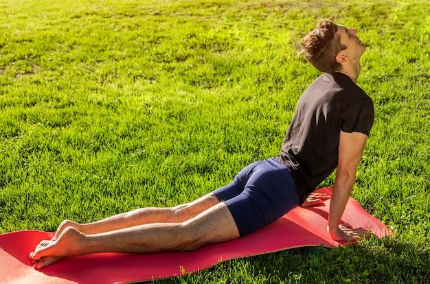 Поза кобры или поза собаки вверх. человек практикующих йогу на коврике в парке
