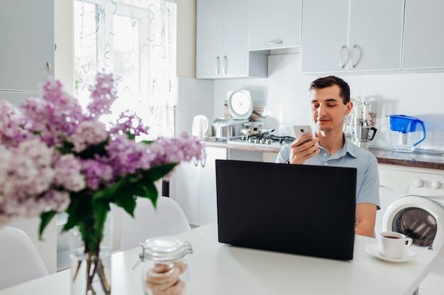 ラップトップとスマートフォンを使用して自宅で仕事青年実業家