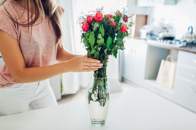 女性は花瓶から枯れたバラの花を取り出します。キッチンで居心地の良さの世話をする主婦。