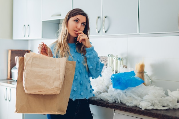 プラスチックまたは紙袋の選択。自宅でエコまたはポリエチレンのパケットを選択する女性主婦