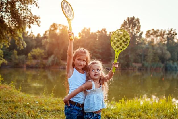 Маленькие девочки весело на открытом воздухе после игры в бадминтон. сестры поднимают ракетки в весеннем парке.