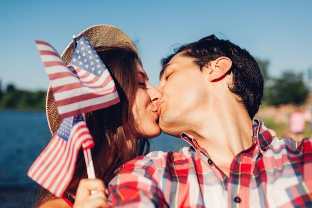 Пара целует и держит флаг сша