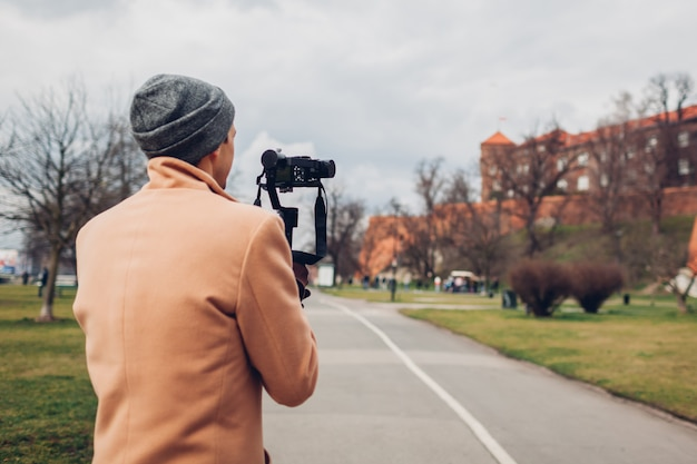 ポーランドのクラクフのヴァヴェル城を撮影するカメラでステディカムスタビライザーを使用して映像を撮影する観光客の男。