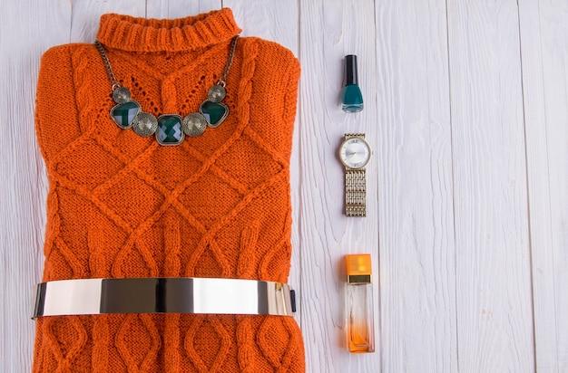 Оранжевый свитер с аксессуарами и косметикой женский наряд