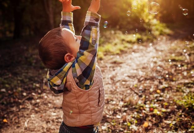 Маленький мальчик ловит пузыри в осеннем лесу
