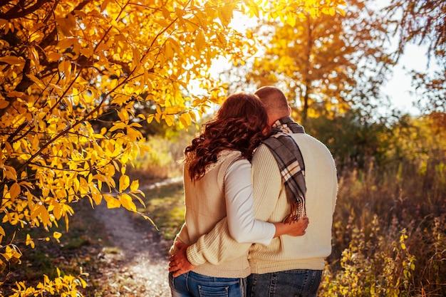 中年夫婦は、カラフルな木々の中で秋の森を抱擁します。