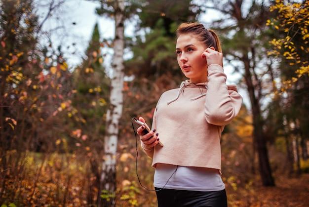 女性ランナーは音楽を聴くために彼女のヘッドフォンを置きます