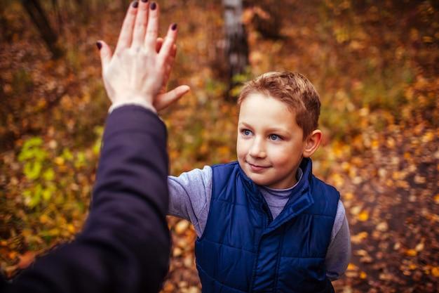 小さな男の子は森で運動した後彼の姉妹にハイタッチを与える