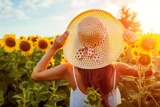 麦わら帽子を保持している咲くひまわり畑を歩いて若い女性。