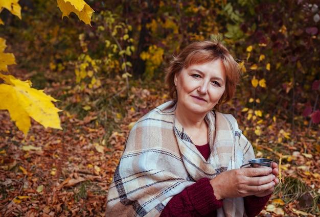 中年の女性は秋の森でお茶を飲みます